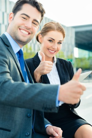 Man and woman in professional clothes smiling