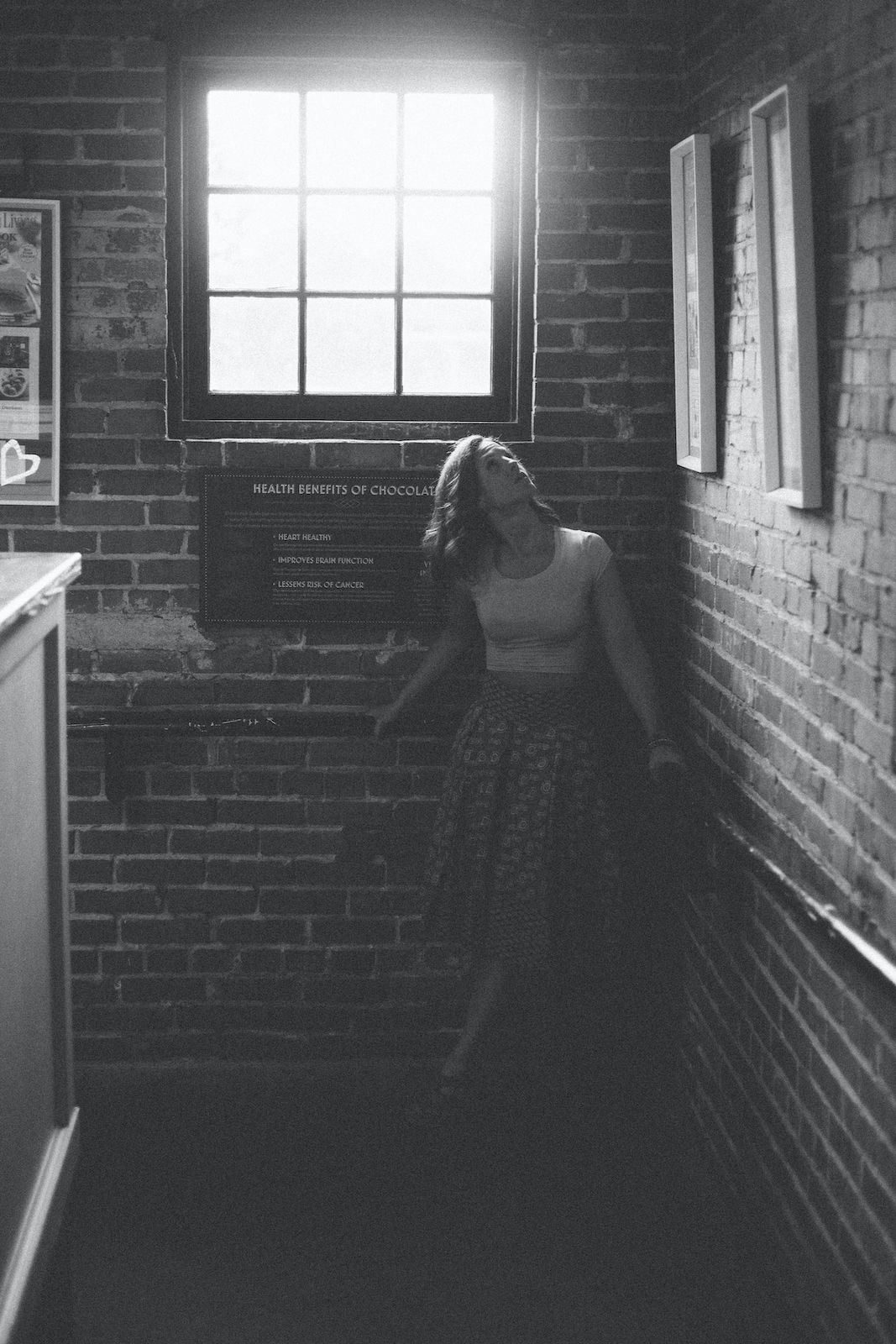 Black and white portrait of Emily with light pouring through window.