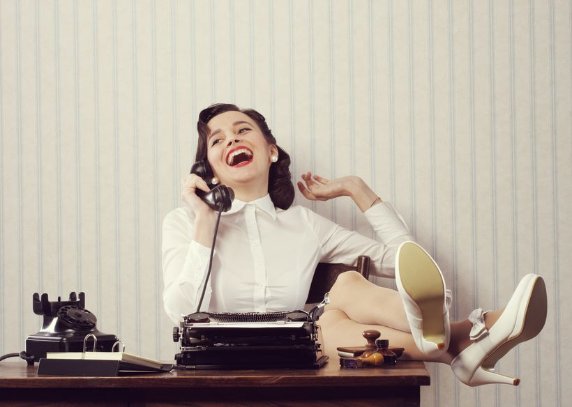 Cheerful woman talking on phone at desk.