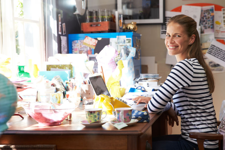 Woman running small business from her home office. She is smiling at her desk with a lot of clutter and objects.