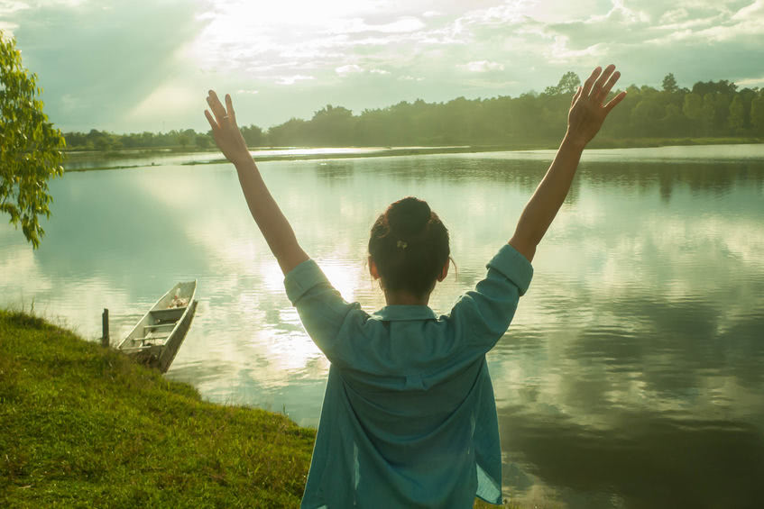Woman standing in front of a lake with her arms raised outwards above her head. The lake's calm water is reflecting the sun and clouds.