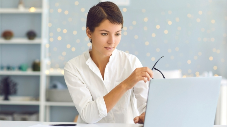 Young professional writer holding a pair of glasses as she works on a laptop..