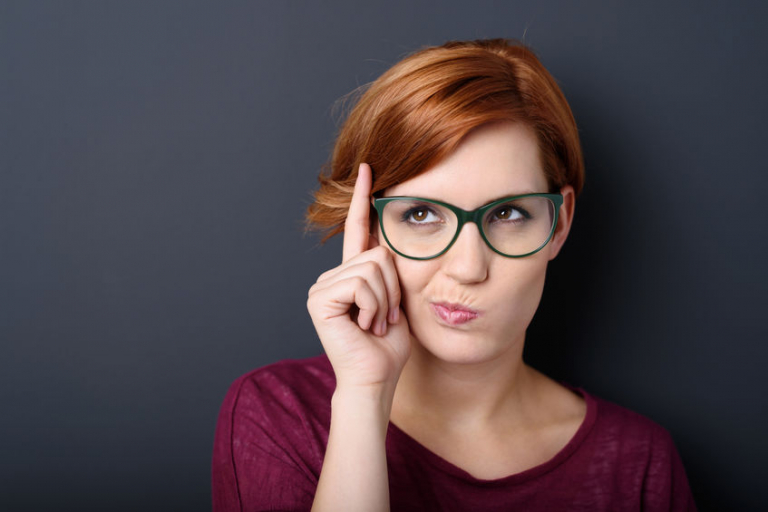 Nerdy scholastic young woman wearing geeky glasses standing thinking with her finger raised and a grimace of concentration in a humorous stereotypical depiction, over a dark background with copyspace.