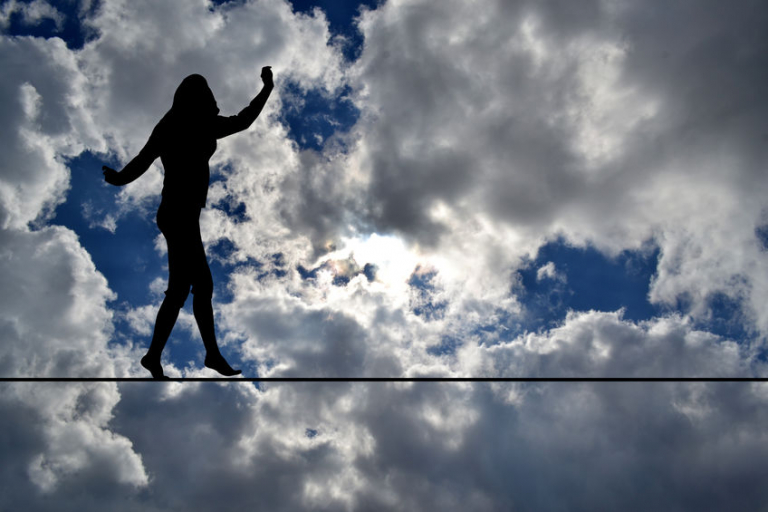 Woman silhouette balancing on rope over blue sky