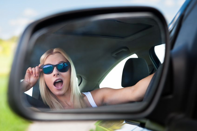Young blonde woman wearing sunglasses driving car