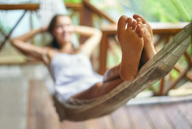 Young beautiful woman relaxing in hammock in a tropical resort. Focus on foot