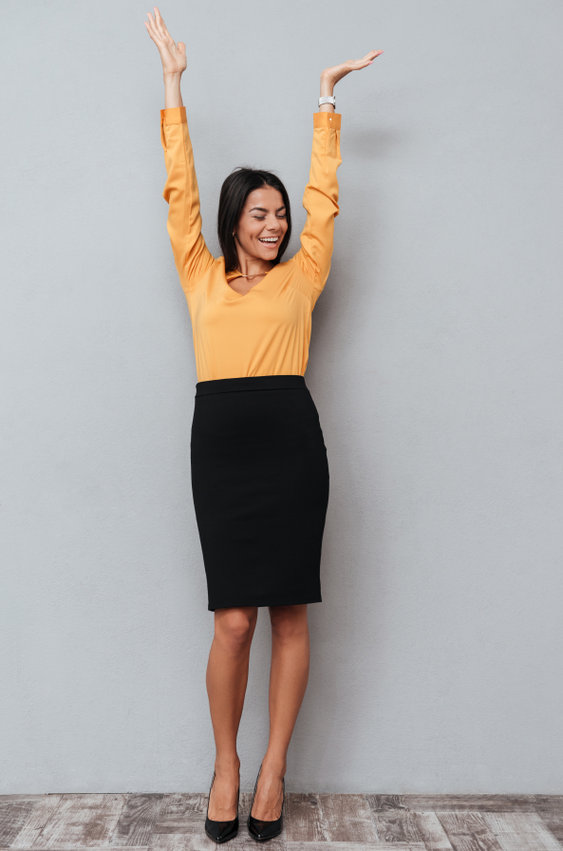 A happy cheerful business woman celebrating success with hands raised