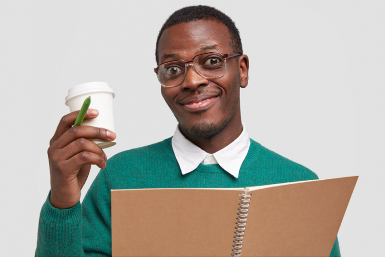 Young man with stubble, wears square spectacles, holds takeaway coffee, pen and notebook, pleased with good working result, isolated over white background.